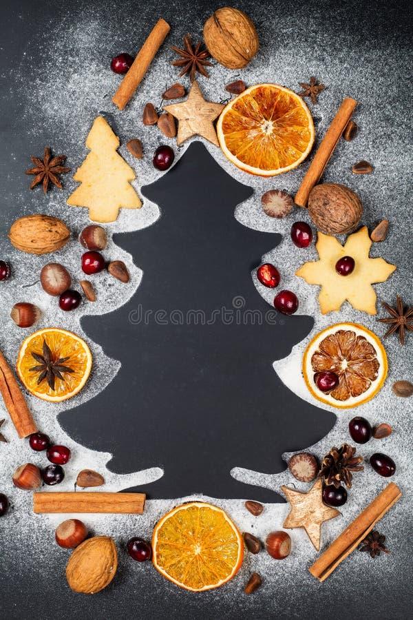 Form des Weihnachtsbaums gemacht vom Puderzucker auf dunklem Hintergrund mit Nüssen, Moosbeeren, Sternanis, Kiefernnüssen, Plätzc stockfotografie