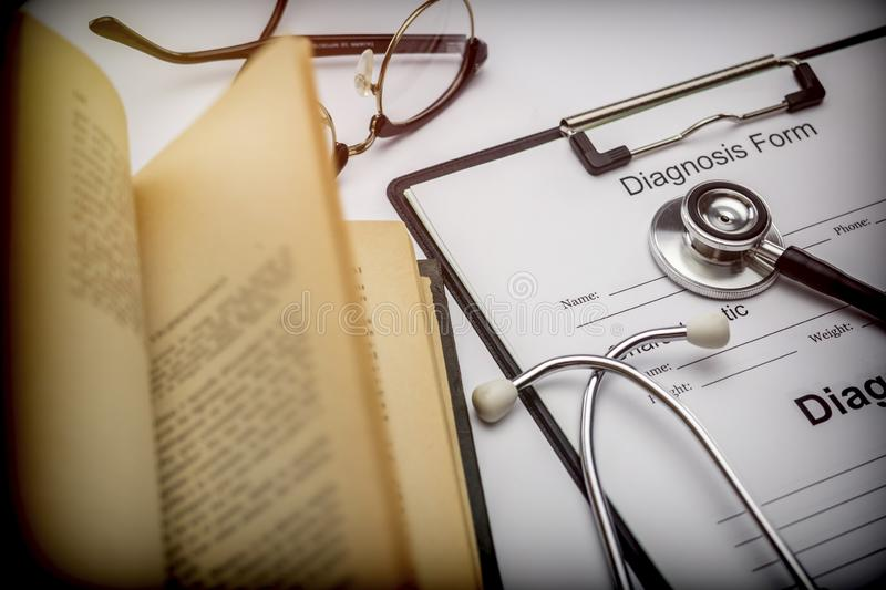 Form of diagnosis next to an old workbook to a stethoscope. Conceptual image stock photos