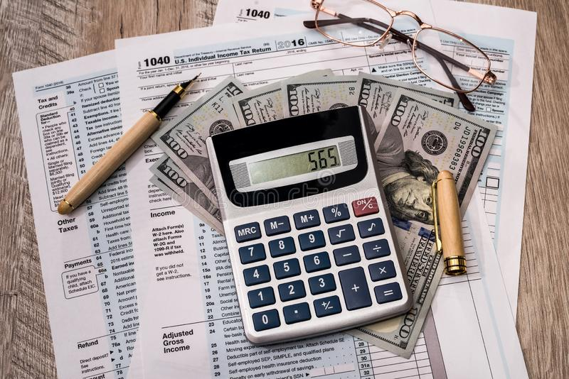 1040 form, dollar banknotes with calculator and pen.  royalty free stock photo