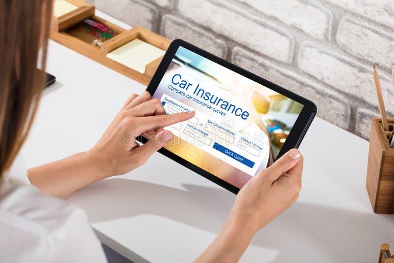 Form för affärskvinnaFilling The Car försäkring på den Digital minnestavlan royaltyfri bild