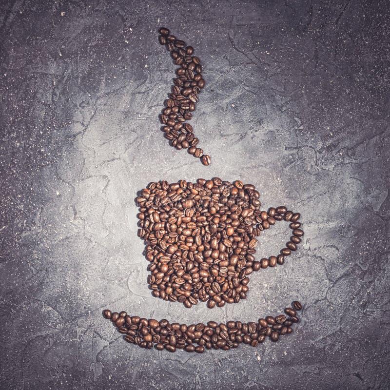 Form för kaffekopp från grillade bönor med ånga på en violett stenbakgrund arkivbilder