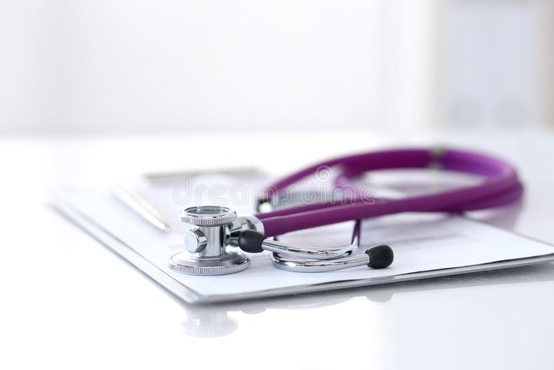 Form för läkarbehandlinghistorierekord som ligger på tabellen med stetoskop- och silverpennan Medicin- eller apotekbegrepp läkaru fotografering för bildbyråer