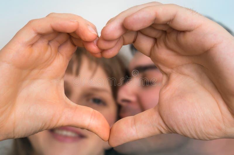 Form för pardanandehjärta med händer och se till och med den royaltyfria foton