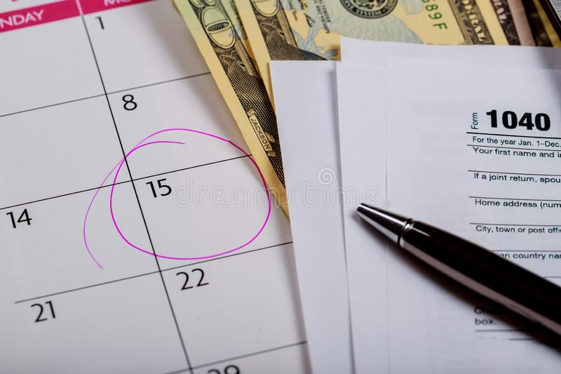form för skatt 1040 med dagen April för pengar-, penn- och datortangentbordskatt arkivbild