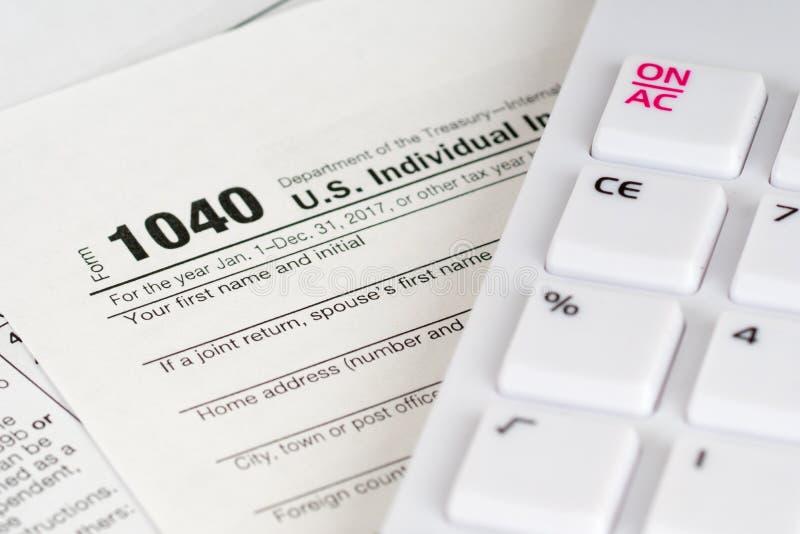 form för skatt 1040 med den vita räknemaskinen arkivbild