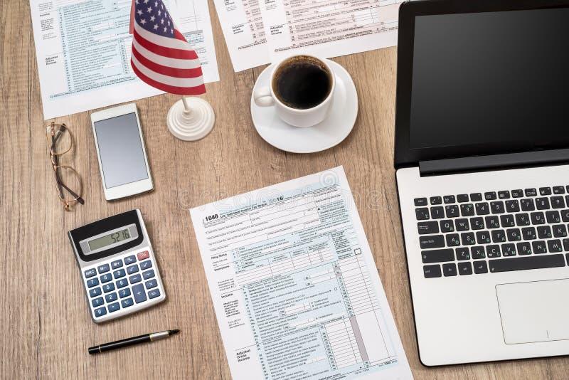 form f?r skatt 1040, b?rbar dator, exponeringsglas, kaffe p? skrivbordet arkivbild