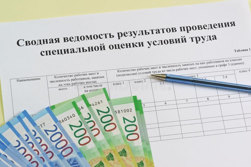 Form in Russian: `Summary of the results of the special assessment of working conditions`. Ballpoint pen and new ruble bills on the table. Summing up the royalty free stock photography