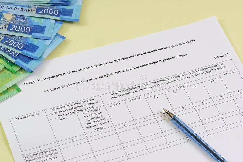 Form in Russian: `Summary sheet of special assessment of working conditions`. And a ballpoint pen. Payment for services rendered to an assessment specialist stock images