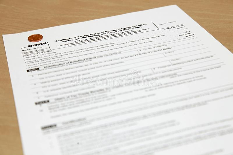 Form W8BEN with a coin. Certificate of foreign status of beneficial owner for United States tax withholding and reporting for individuals stock image