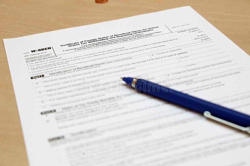 Form W8BEN with a pen. Certificate of foreign status of beneficial owner for United States tax withholding and reporting for individuals with a pen on the table royalty free stock image