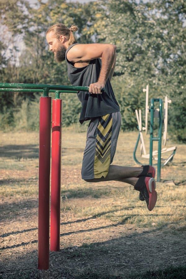Formação ao ar livre Homem que faz a formação dos mergulhos do bíceps e do tríceps fotografia de stock royalty free