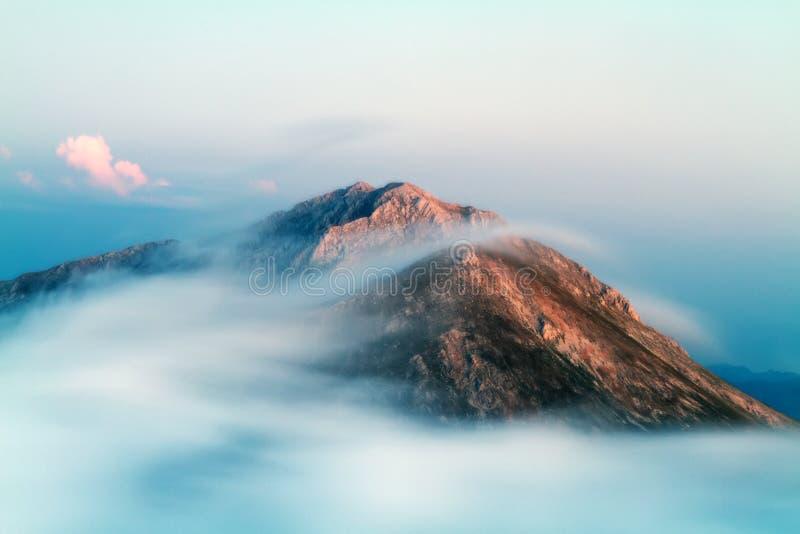 Formação e movimento das nuvens sobre picos de montanhas fotografia de stock royalty free
