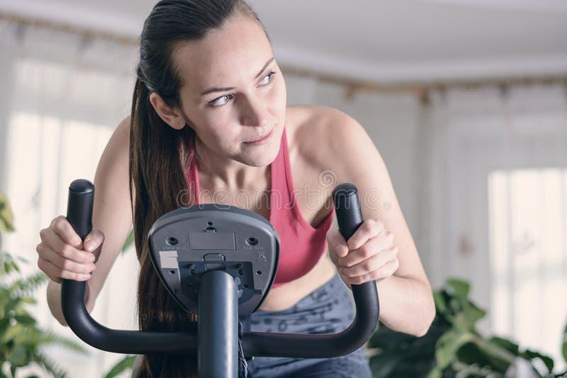 A formação europeia da mulher cardio- dá certo em casa na bicicleta de exercício Conceito para a perda de peso Moça motivado e fo fotografia de stock royalty free