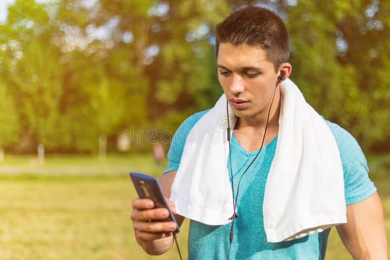Formação running da aptidão do app do smartphone dos esportes do homem novo exterior fotografia de stock