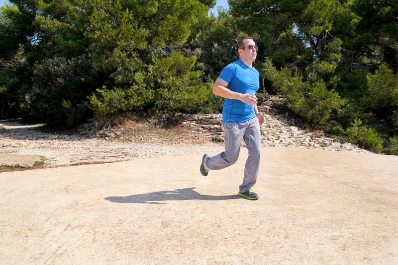 Formação running do corredor do atleta do homem exterior nos desportistas running do corredor da floresta que vestem o sportswear imagem de stock royalty free