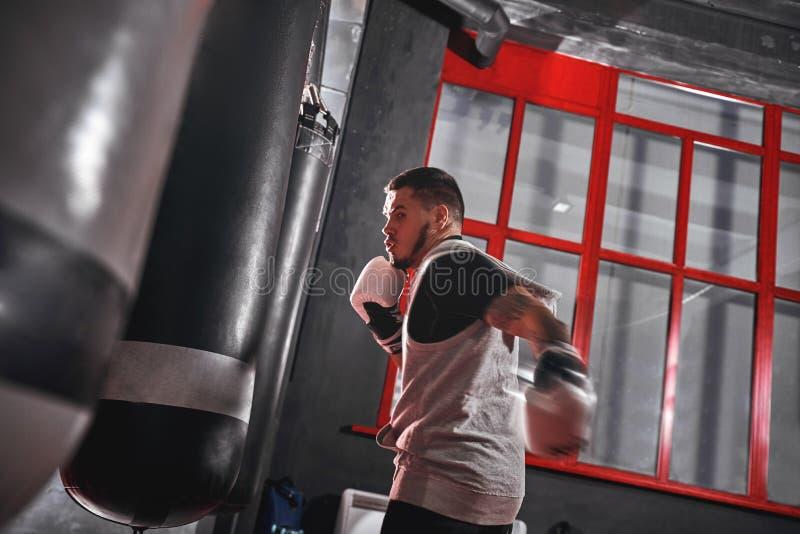 Formação a ser o melhor atleta muscular Tattooed no treinamento da roupa dos esportes duro no saco pesado do perfurador antes da  fotos de stock royalty free