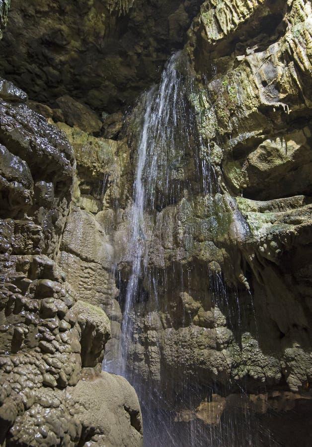 Formações de rocha Geological e cachoeira em uma caverna subterrânea imagens de stock royalty free