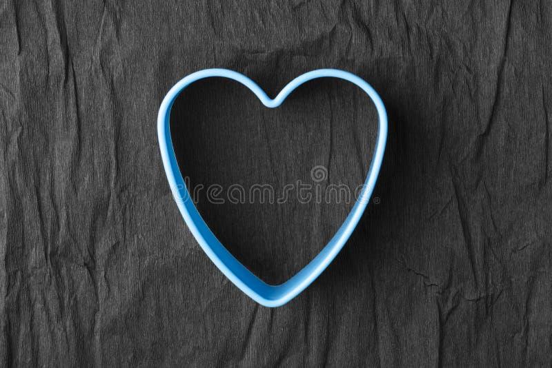 Forma azul do coração no papel preto amarrotado imagem de stock