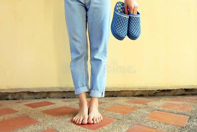 Forma azul dos falhanços de aleta As sandálias e a calças de ganga azuis do desgaste de mulher estão no fundo do assoalho de telh foto de stock royalty free