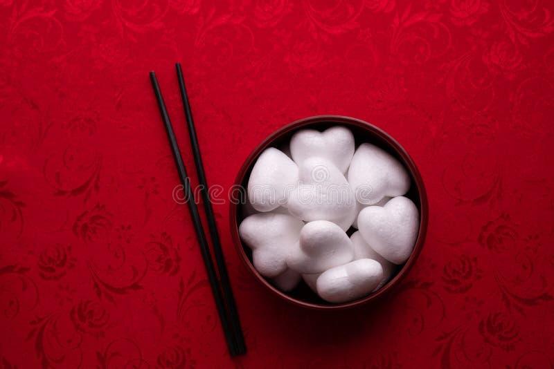 Forma bianca del cuore sul piatto con fondo rosso, celebrazione di festa di San Valentino immagine stock