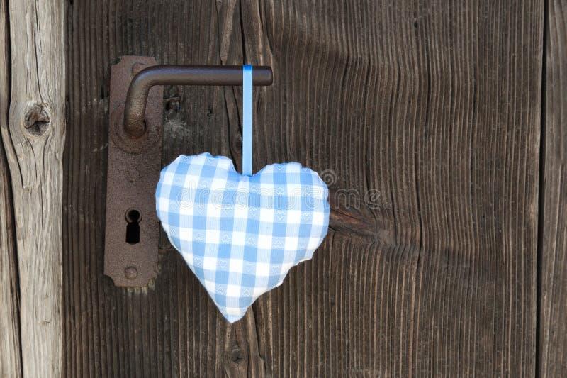 Forma blu a quadretti del cuore che appende sulla maniglia di porta per nozze, b fotografia stock libera da diritti