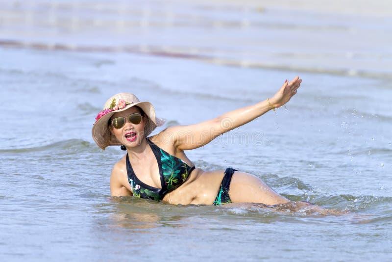 Forma da mulher enorme com a onda do jogo do biquini na praia foto de stock