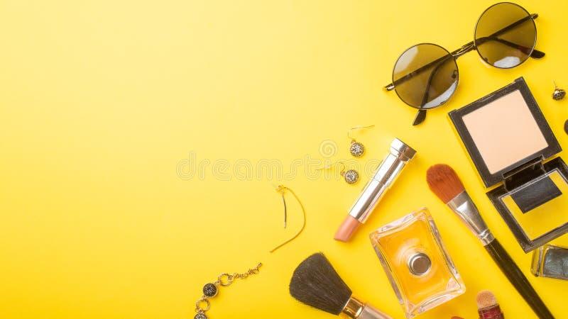 A forma das mulheres, e a beleza Os acess?rios e os cosm?ticos das mulheres em um fundo amarelo bandeira imagem de stock royalty free