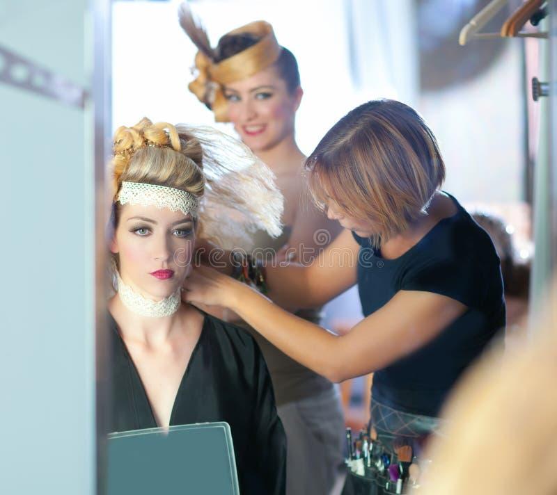 Forma de bastidores do hairdressing com artista de composição imagem de stock