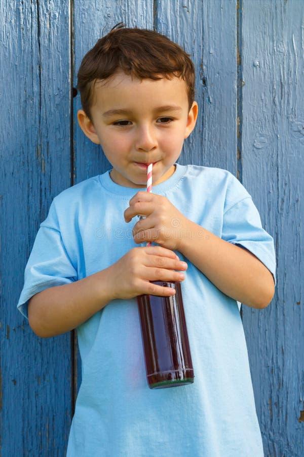 Forma de consumición del retrato de la bebida de la limonada de la cola del niño pequeño del niño del niño imagen de archivo