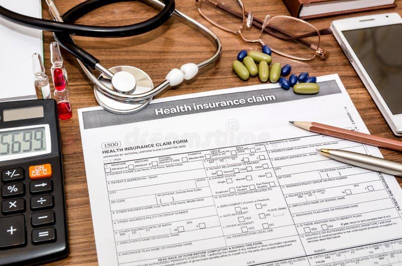 Forma de demanda del seguro médico con el estetoscopio en el tablero, jeringuilla imagen de archivo