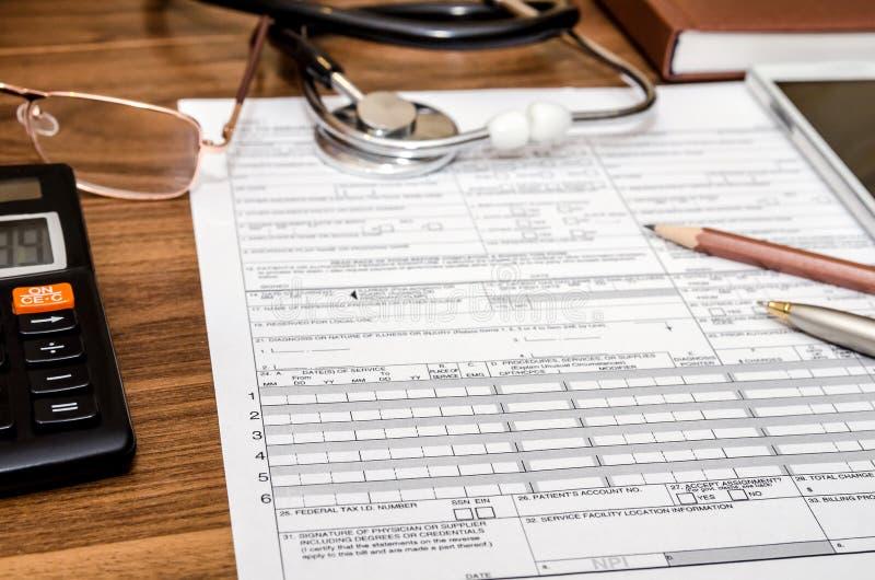 Forma de demanda del seguro médico con el estetoscopio en el tablero, jeringuilla, calculadora fotografía de archivo