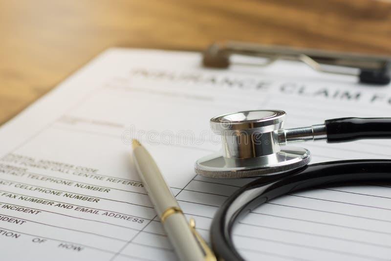 Forma de demanda del seguro médico con el estetoscopio en el selec de madera de la tabla imagenes de archivo