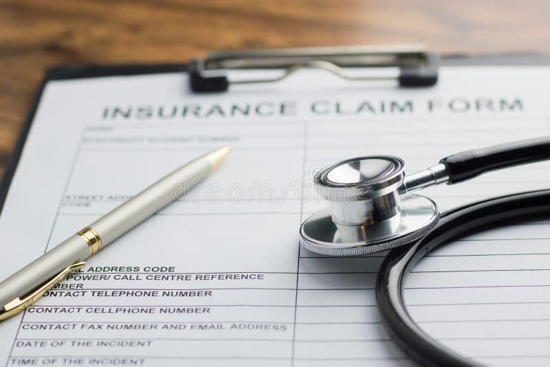 Forma de demanda del seguro médico con el estetoscopio en el selec de madera de la tabla fotos de archivo libres de regalías