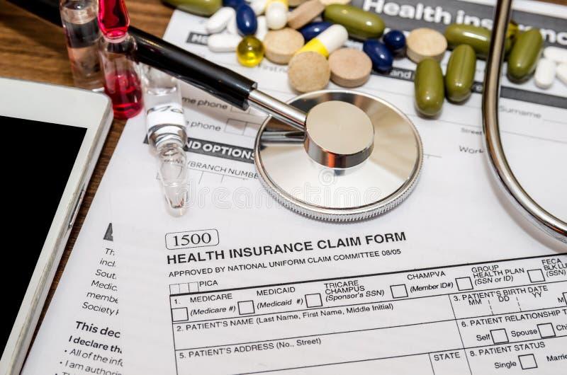 Forma de demanda del seguro médico con las píldoras, jeringuilla, teléfono móvil, estetoscopio fotografía de archivo