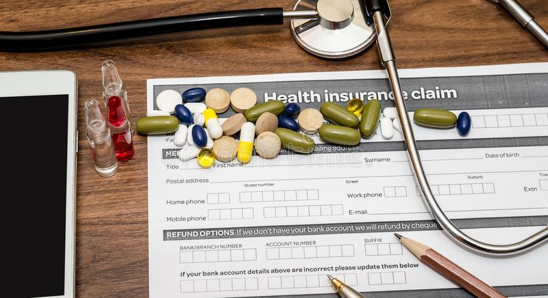Forma de demanda personal del seguro médico con las píldoras, jeringuilla, teléfono móvil, estetoscopio imagenes de archivo