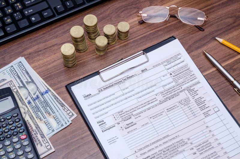 forma de impuesto 1040A con el dinero, calculadora, pluma fotos de archivo