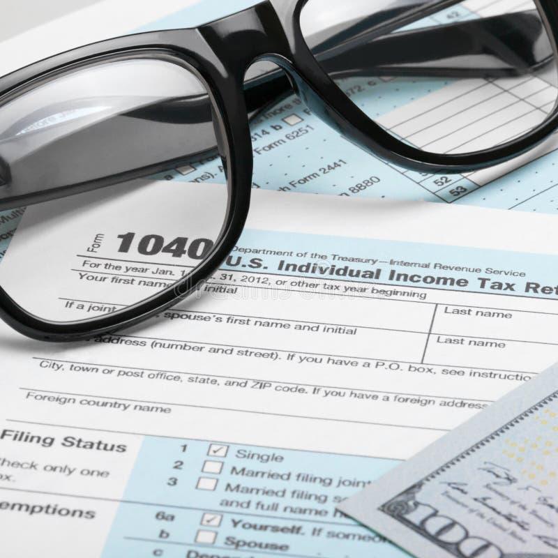 Forma de impuesto de los Estados Unidos de América 1040 con los dólares y los vidrios - ratio 1 a 1 foto de archivo