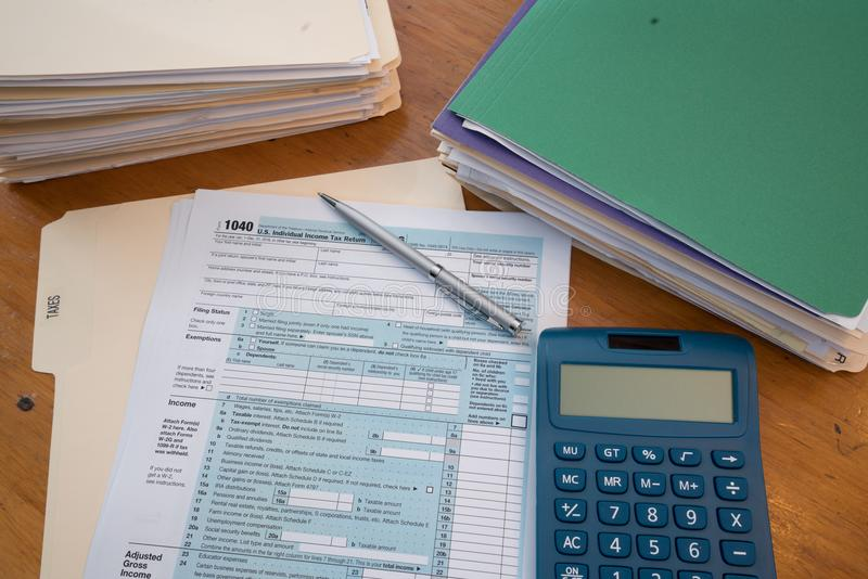 Forma de impuesto del IRS con las carpetas, la calculadora y la pluma foto de archivo libre de regalías