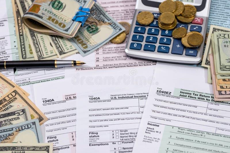 Forma de impuestos de la limadura, dinero, calculadora y pluma fotografía de archivo