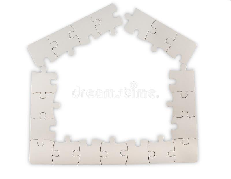 Forma de la casa hecha de pedazos del rompecabezas foto de archivo libre de regalías
