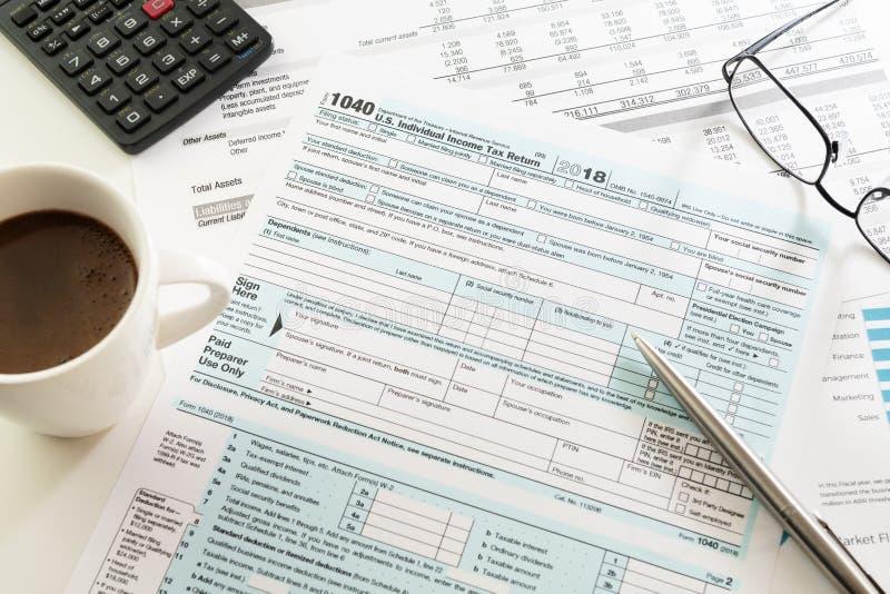Forma de la declaración sobre la renta con la taza, la calculadora, los vidrios y la pluma del café express en la tabla foto de archivo libre de regalías