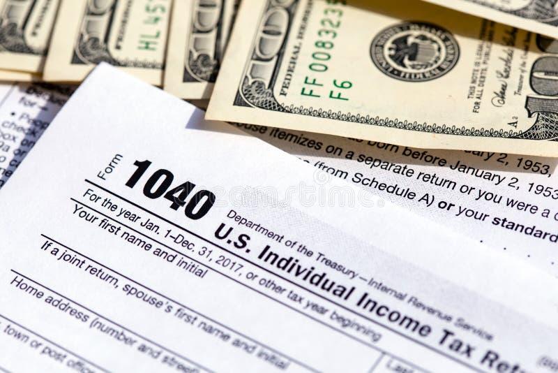 Forma de la declaración sobre la renta del individuo de los E.E.U.U. 1040 con cientos billetes de dólar foto de archivo