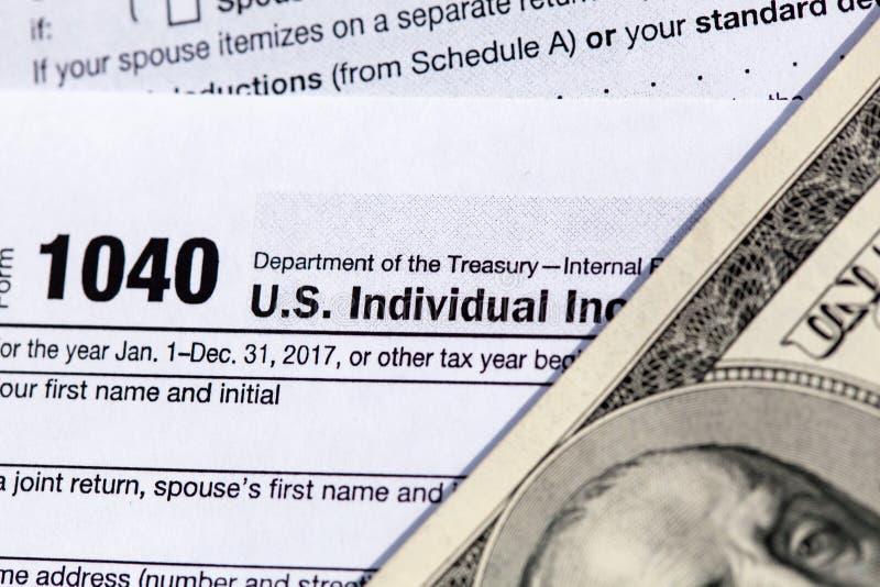 Forma de la declaración sobre la renta del individuo de los E.E.U.U. 1040 con cientos billetes de dólar imágenes de archivo libres de regalías