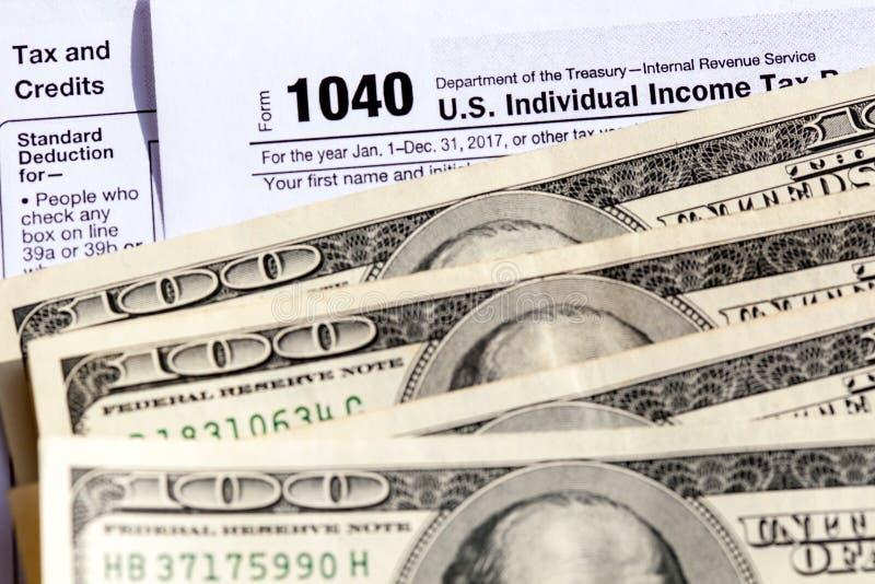 Forma de la declaración sobre la renta del individuo de los E.E.U.U. 1040 con cientos billetes de dólar fotografía de archivo libre de regalías