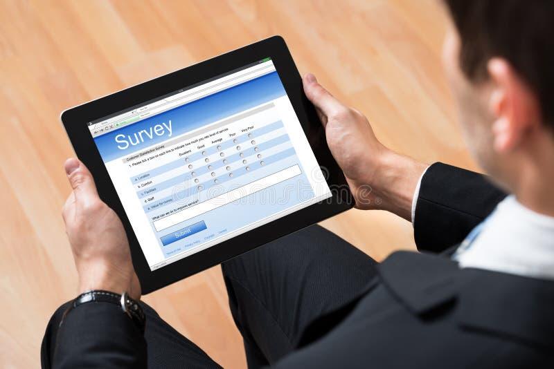 Forma de la encuesta sobre Looking At Online del hombre de negocios fotos de archivo