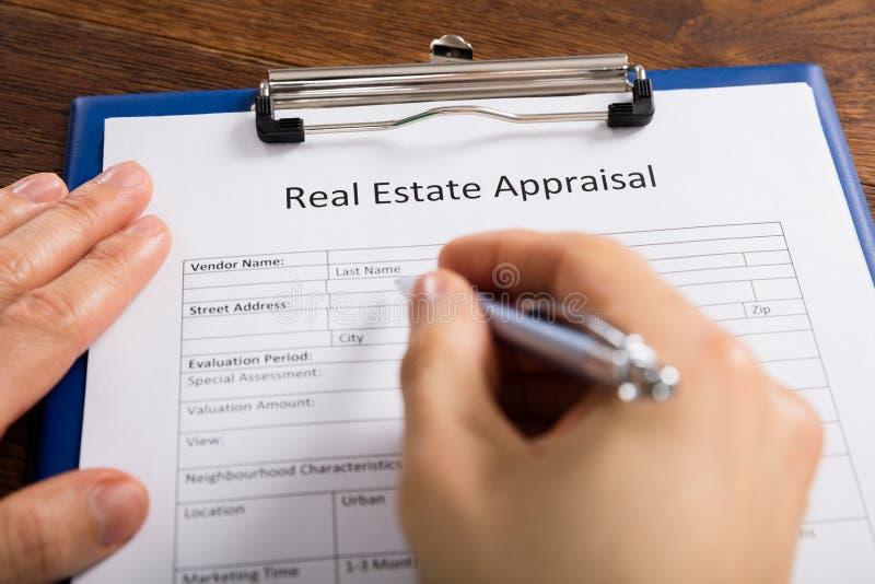 Forma de la valoración de Person Hand Filling Real Estate imagenes de archivo