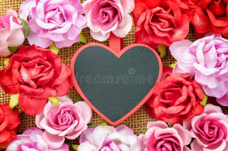 Forma de madeira vazia do coração da etiqueta com rosas pequenas fotos de stock royalty free