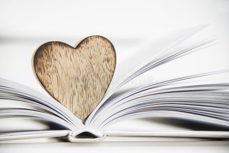 Forma de madera del corazón en un libro abierto Cierre del concepto de la lectura del amor para arriba imágenes de archivo libres de regalías