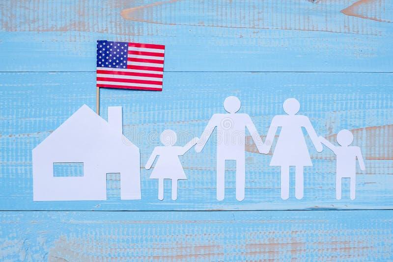 Forma de papel de la gente o del familia y casera con la bandera de los Estados Unidos de América en fondo de madera azul Día de  fotos de archivo