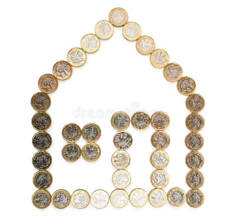 Forma de una casa hecha de monedas de oro foto de archivo